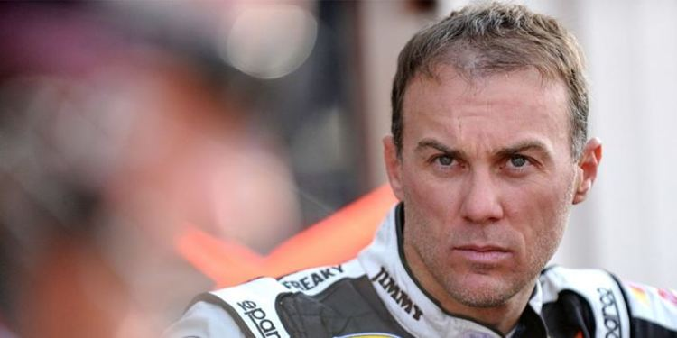 Kevin Harvick looking up, with the background blurred and you can only see his face