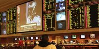 Bettor staring at betting board in sportsbook