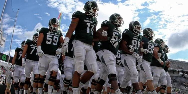Michigan State team walking into the field