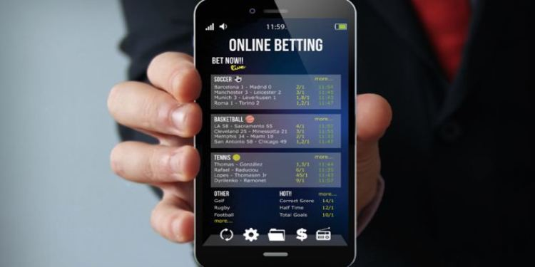Man Holding Smartphone while showing a betting site on his mobile screen