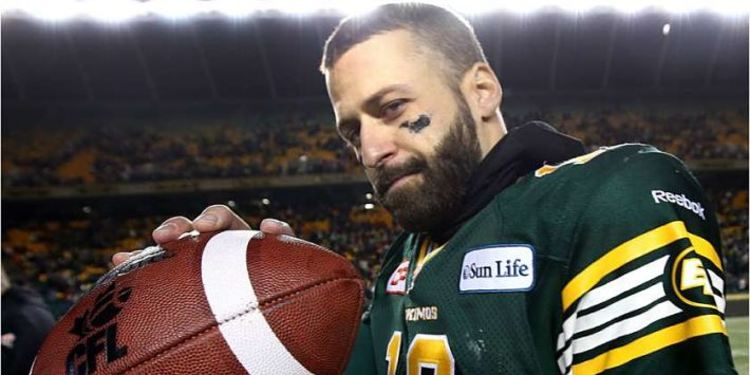 Mike Reilly holding the ball and posing for a picture