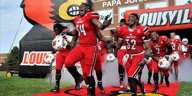 Louisville Cardinals team running into the field