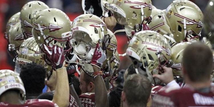 Florida State Seminoles teammates raising their helmet