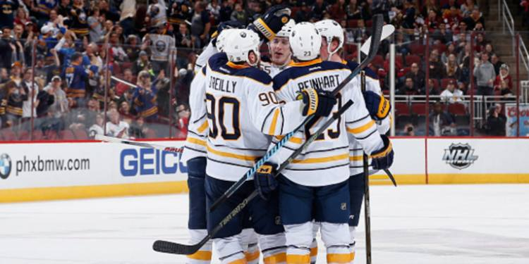 The Buffalo Sabres celebrate as a team in the rink