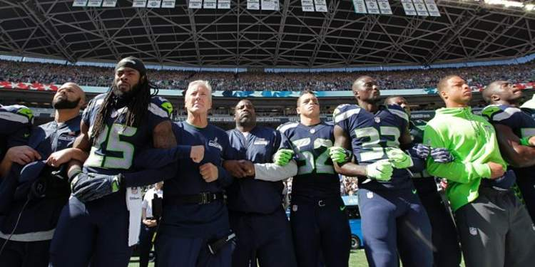Seattle Seahawks players and coaches stand and link arms during the singing of the National Anthem