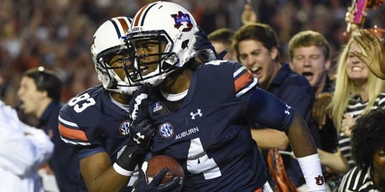 Auburn Tigers player holding the ball while another one seems to be celebrating him