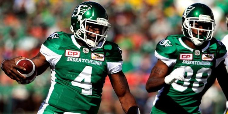Saskatchewan Roughriders running during a game, one with the ball