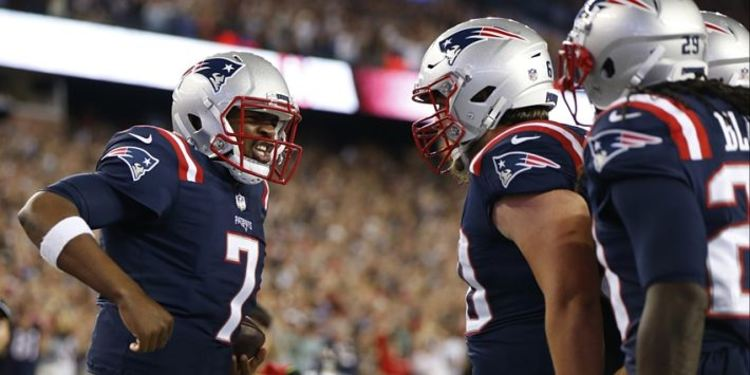 New England Patriots' Jacoby Brissett celebrating with his teammates during a game
