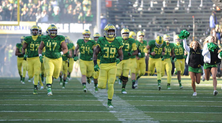 Oregon Ducks Players run onto the field