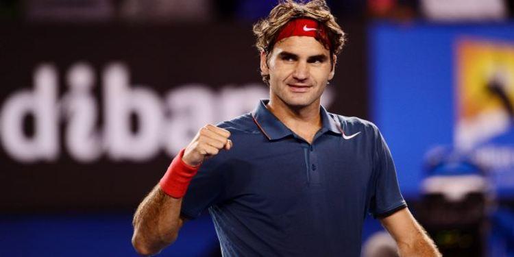 Roger Federer on the tennis court wearing a green shirt