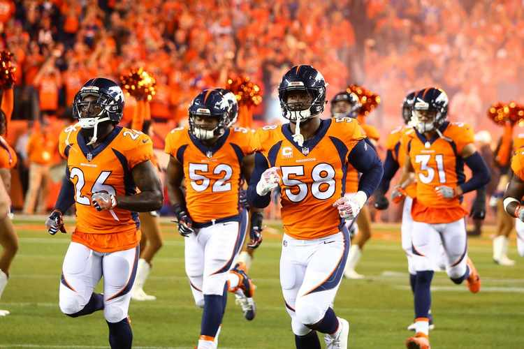 Denver Broncos players running into filed